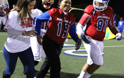 Malone storms field with football team after remarkable recovery