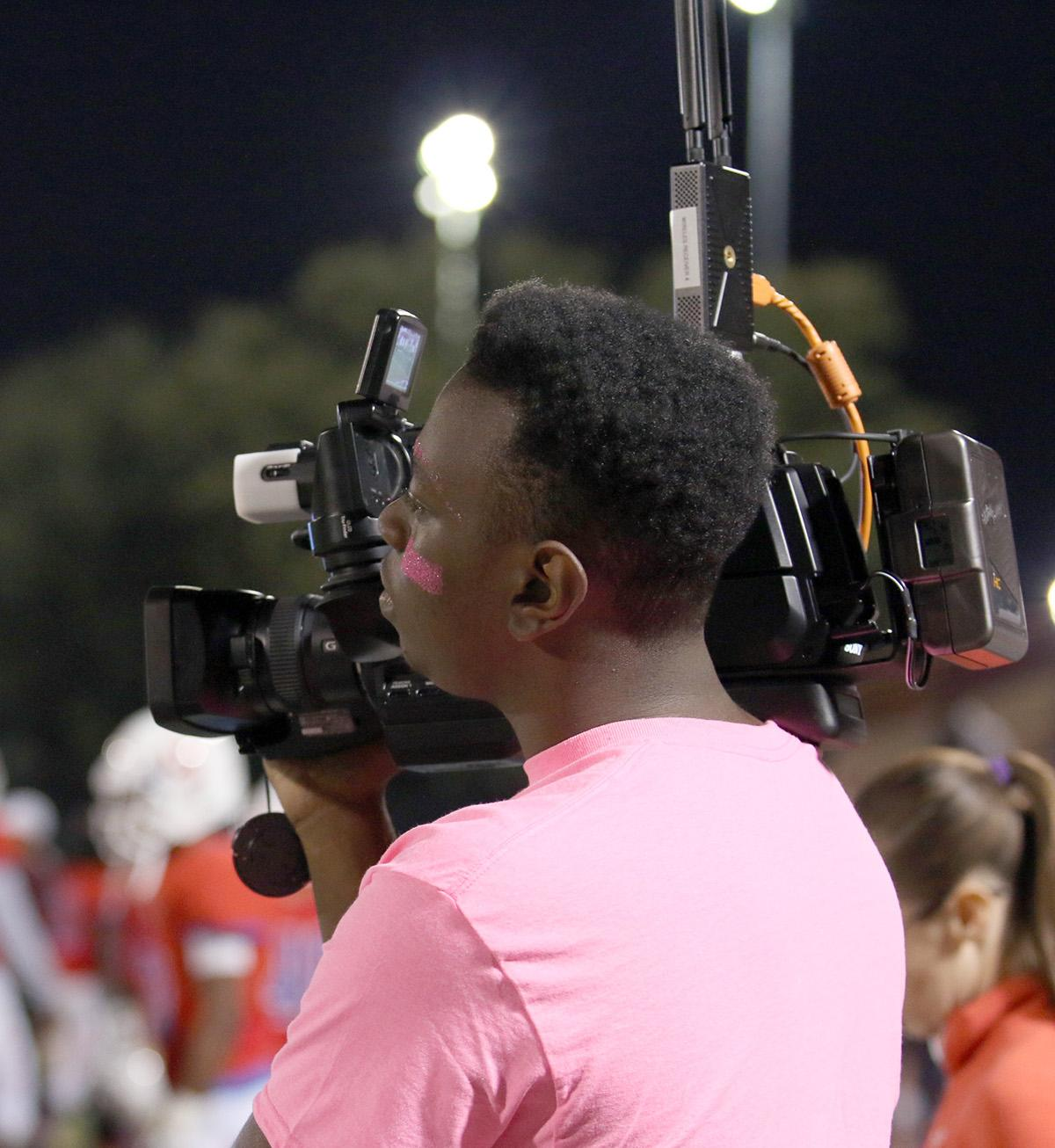 Ricardo Martin works a video camera on the field of the Duncanville Vs. DeSoto football game for the scoreboard. (Emlyn Almanza photo)