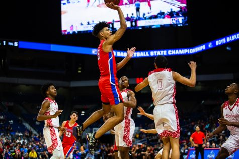 Junior Micah Peavy (5) goes up for a shot against North Shore in the basketball state semi final.