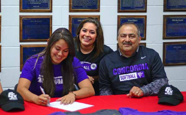 Senior Valerie Gonzales signs her letter of intent to play for Concordia University as her parents look on.  (Cody Rogers Photo)