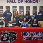 Jazmine Washington signs her letter of intent to play college volleyball with her family and coaches by her side.