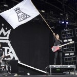 Guitarist Pete Wentz waves a Fall Out Boy flag over the crowd as lead singer Patrick Stump takes a vocal solo. (Credit to Billboards Music.)