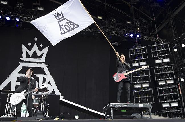 Guitarist+Pete+Wentz+waves+a+Fall+Out+Boy+flag+over+the+crowd+as+lead+singer+Patrick+Stump+takes+a+vocal+solo.+%28Credit+to+Billboards+Music.%29