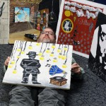 Mr. Gawedzinski poses underneath one of his former student's decorated tiles to display how he, too, feels like an Invisible Man. (Alisha Nichols photo)