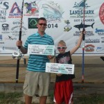 Joseph and Jackson pose with their checks from the 2014 Shark-A-Thon tournament. Joseph, left, placed second, and his son, right, placed third in the kids division.