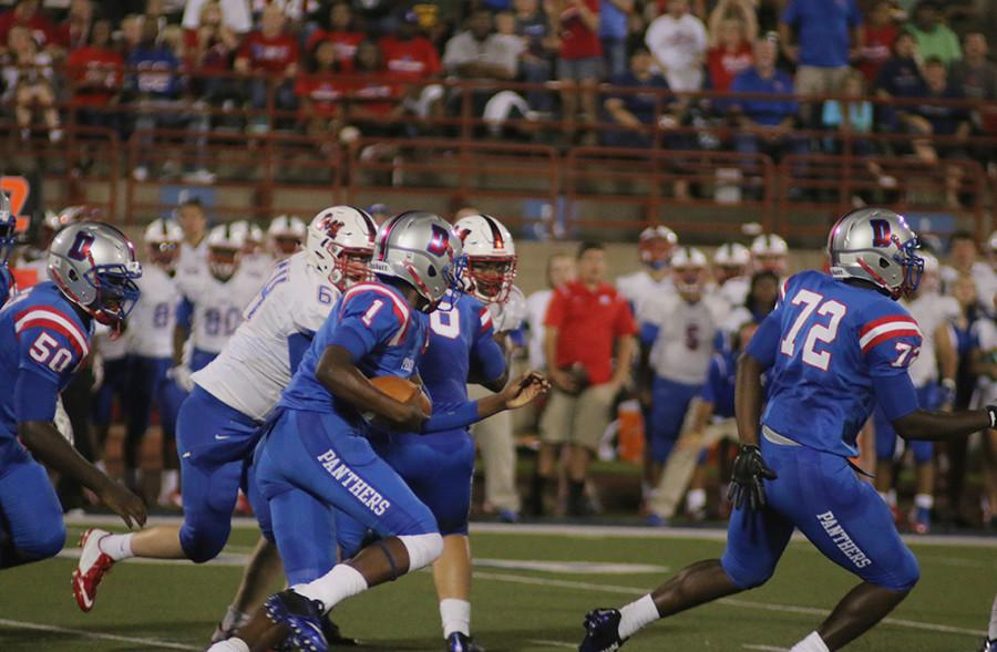 Varsity quarterback Mike Meyers scrambles with the ball in game against Waco Midway. The Panthers went on to lose this game at home. (photo by Ricardo Martin)