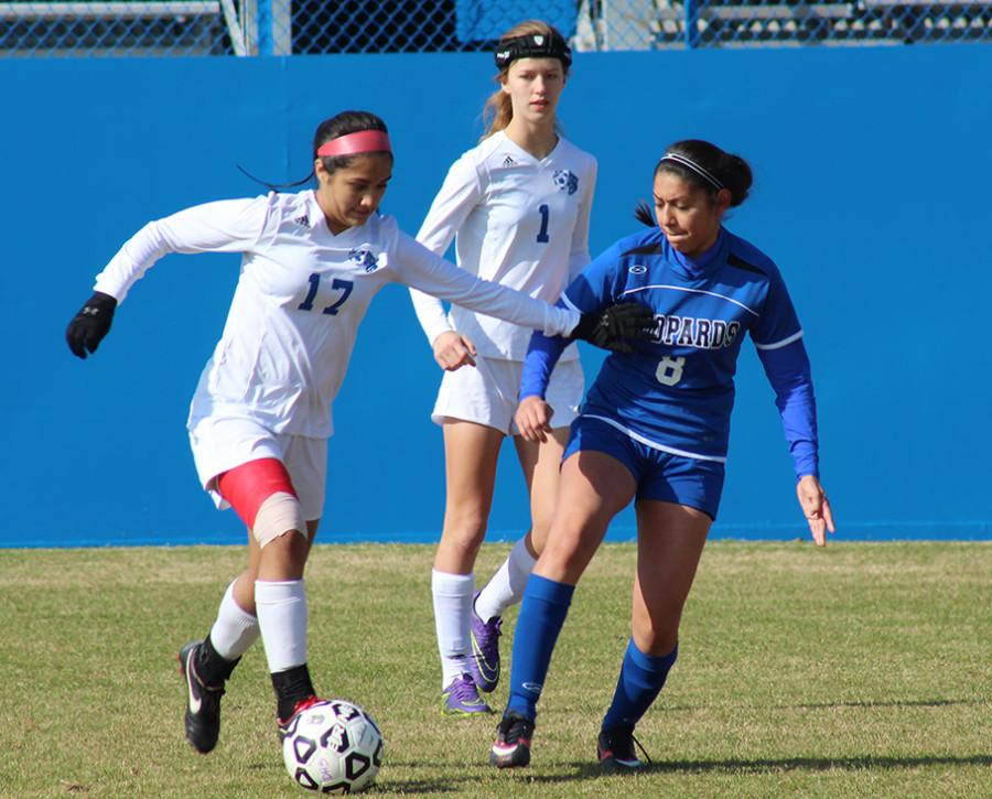 Miran Garza pushes the ball forward as Corine Daniels follows against a tough opponent in tournament play. (Ruth Thunderhawk photo)