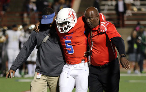 Panther Head Coach Reginald Samples assist trainer Alec Hawkins with giving starting quarterback Jaylin Nelson some support off the field after his season ending injury. (Jose Sanchez photo)