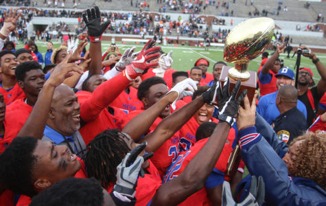 Duncanville Principal Tia Simmons presents the Regional Semi-Finals football trophy to Coach Reginald Samples and the team after their 32-27 win over Arlington Bowie. (Jose Sanchez photo)