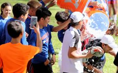 Runners smash assistant coach Moses Pena with ice water after the announcement of the teams district championship. (Ricardo Martin photo)