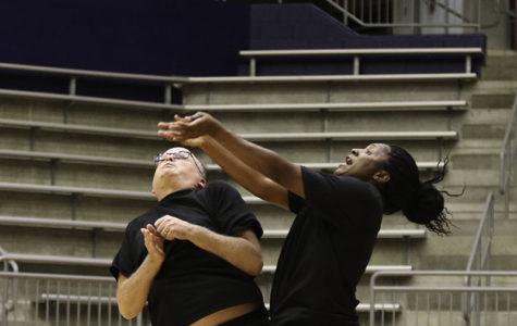 Art teacher Yolanda Harris and History teacher David Wallner collide while trying to push the ball over the net against the students in the Faculty vs. student Powderbuff volleyball game. (Ruth Thunderhawk photo)