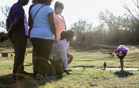 Senior Storm Malone kneels at the foot of his mother and sister's graves a few days after his mother's birthday. Every time he visits the grave he remembers the day four years ago when their lives were cut short in a tragic domestic violence shooting. Storm said he just wants to remember the joy they both brought to his life. (Alexis Rosebrock Photo)