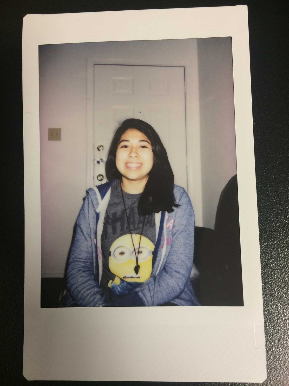 Alondra Gonzales takes a snapshot with a Polaroid while visiting a friends house.
