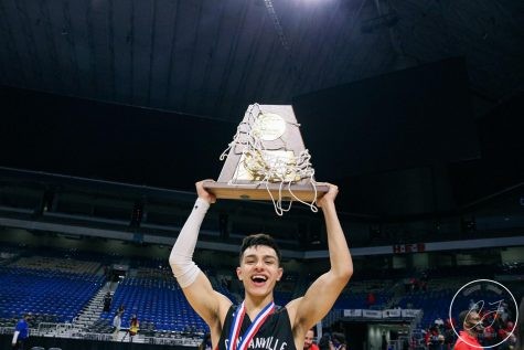 Senior Juan Reyna holds up the UIL 6A Championship trophy.